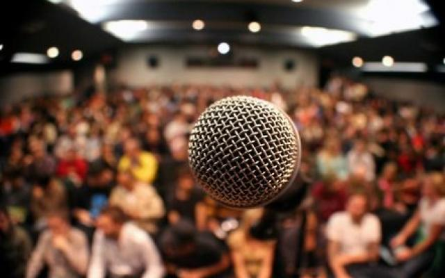 Image of microphone in crowded lecture hall